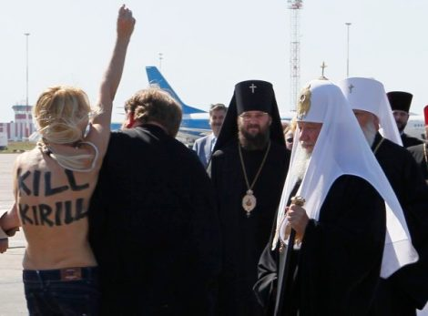 Security guards detain an activist from women's rights group Femen as she protests against the visit of the head of the dominant Russian Orthodox Church, Patriarch Kirill, in Ukraine in Borispol airport