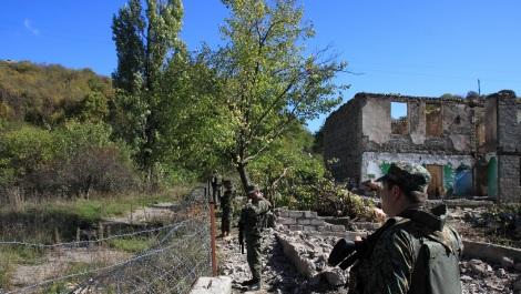 Soldats géorgiens postés à la frontière sud-ossète. En arrière-plan, une maison incendiée par son propriétaire.